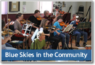 Button image showing the BSIC fiddle orchestra that links to the Blue Skies in the Community website